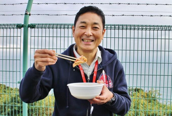 森田泰弘さん。ミッションロゴの大きなワッペンがかっこいいですね。 「えっがね」の行列に並び、「これを食べたらエネルギー充填120%だね。」とはりきっていらっしゃいました。